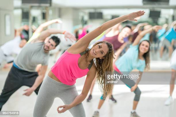 pretty gym instructor guiding her class to stretch all looking very happy - aerobics stock pictures, royalty-free photos & images