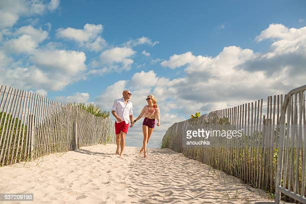 pretty happy couple going to the beach - miami beach stock pictures, royalty-free photos & images