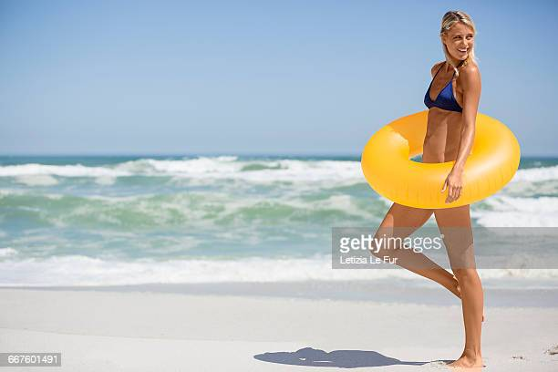 Pretty happy woman enjoying on beach with a inflatable ring