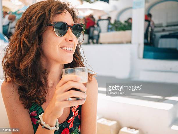 Pretty happy woman holding glass of iced coffee