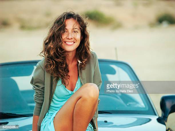 Pretty happy woman sitting over convertible car