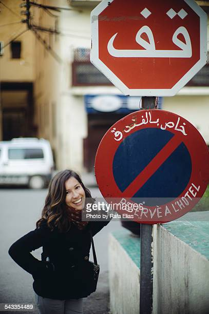 Pretty happy woman standing by traffic signs