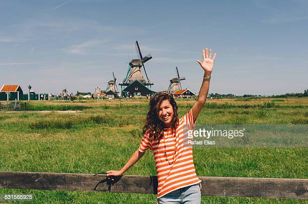 pretty happy woman waving in dutch landscape - traditional windmill stock photos and pictures
