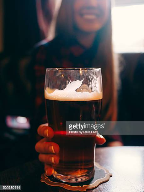 pretty happy young woman holding a pint of beer in pub - ale stock pictures, royalty-free photos & images