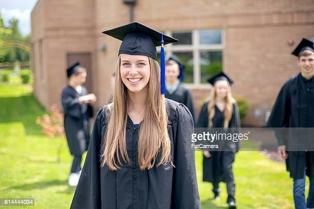 Pretty high school female graduate smiling