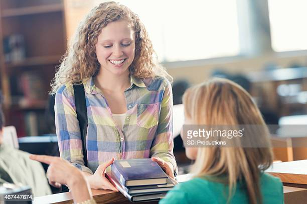 Pretty high school girl returning stack of textbooks in library