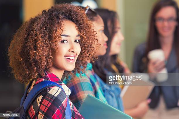 pretty high school girl standing with a group at school. - beautiful ethiopian girls stock photos and pictures