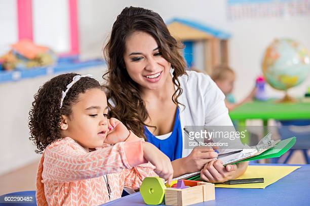 pretty hispanic daycare teacher assesses little girl playing blocks - the_writer's_block stock pictures, royalty-free photos & images