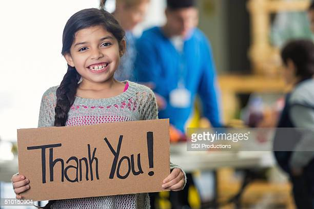 pretty hispanic girl holds 'thank you!' sign in soup kitchen - charitable donation stock pictures, royalty-free photos & images