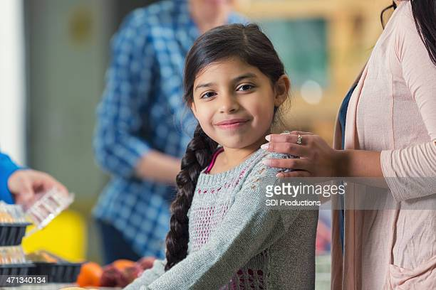 Pretty Hispanic little girl in line at food bank kitchen