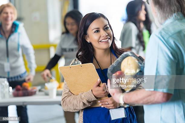 pretty hispanic woman volunteering, leading food donation drive - depression bread line stock pictures, royalty-free photos & images