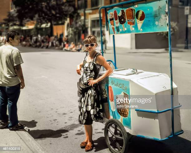 CONTENT] A pretty Ice Cream vendor awaits the crowds arriving for the Carifesta parade in downtown Montreal
