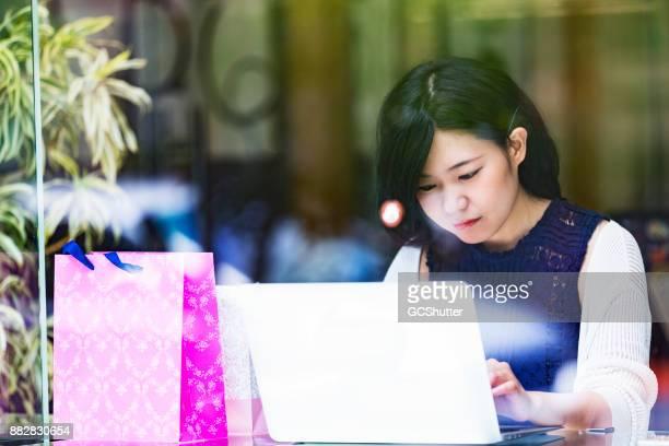 美しい日本の女の子がカフェでラップトップに取り組んで