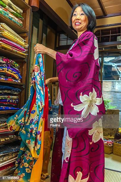 Pretty Japanese Woman Choosing Purple Kimono in Kyoto, Japan