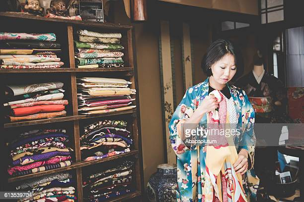 Pretty Japanese Woman Choosing Yellow Kimono in Kyoto, Japan