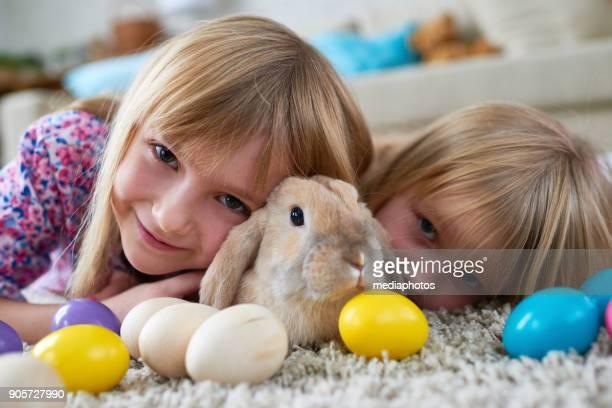 Hübsche Kinder Kommunikation mit Kaninchen zu Ostern