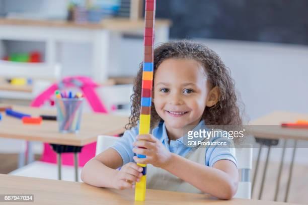 Pretty kindergarten schoolgirl plays with blocks