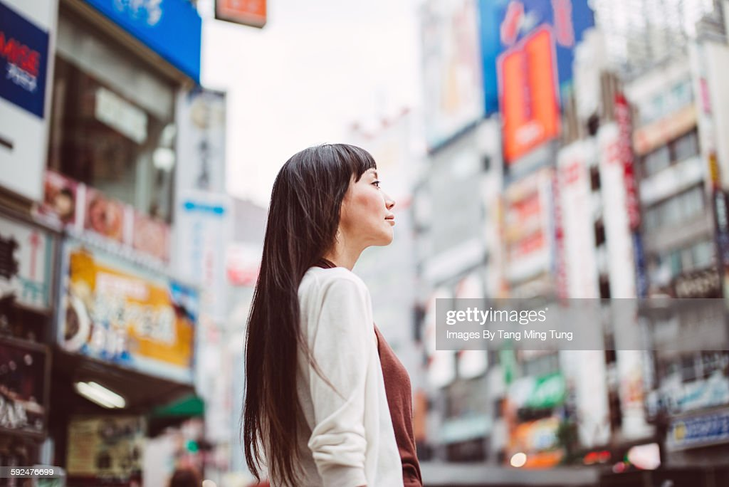 Pretty lady looking at the distance on the street : Stock Photo