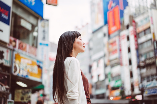 Pretty lady looking at the distance on the street - gettyimageskorea
