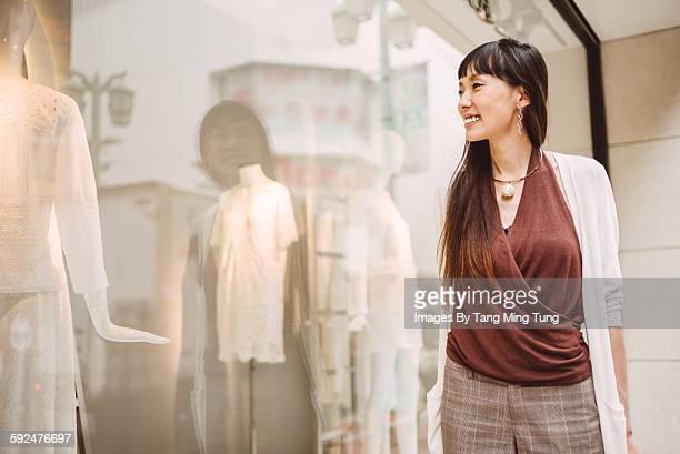 Pretty lady looking at window display joyfully