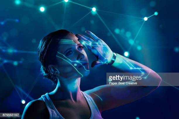 a pretty lady studying constellations and star formations that are projected through a hologram - projektion stock-fotos und bilder