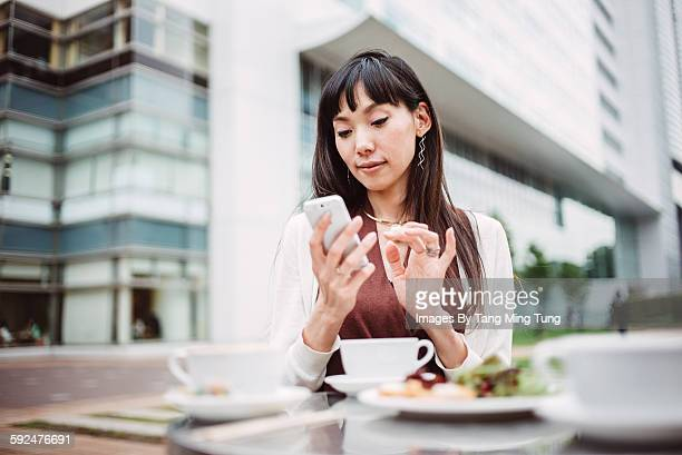 Pretty lady using smartphone in outdoor cafe