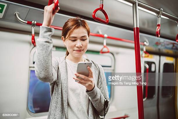 Pretty lady using smartphone in subway joyfully