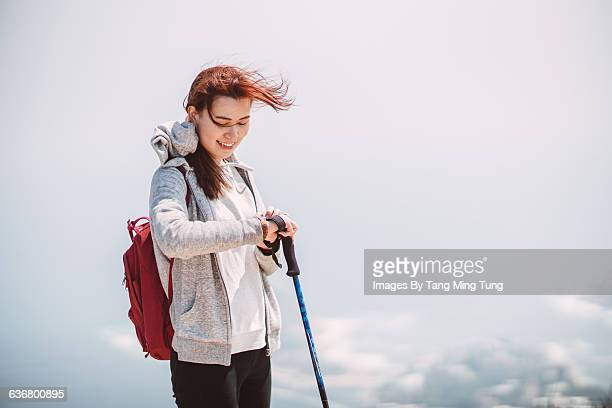 Pretty lady using smartwatch joyfully while hiking