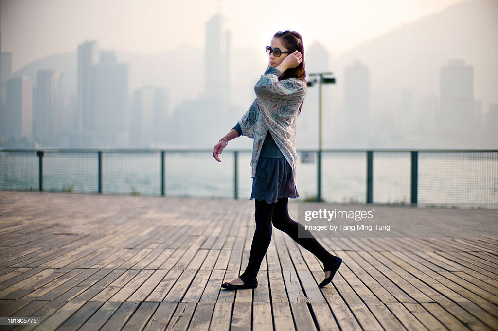 Pretty lady walking on the pier dock during sunset : Stock Photo