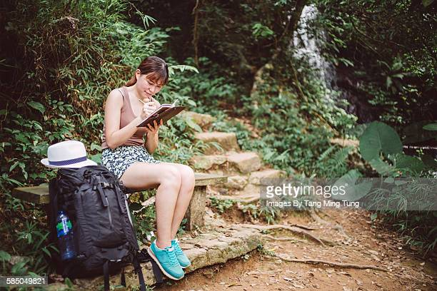 Pretty lady writing travelling notes during travel