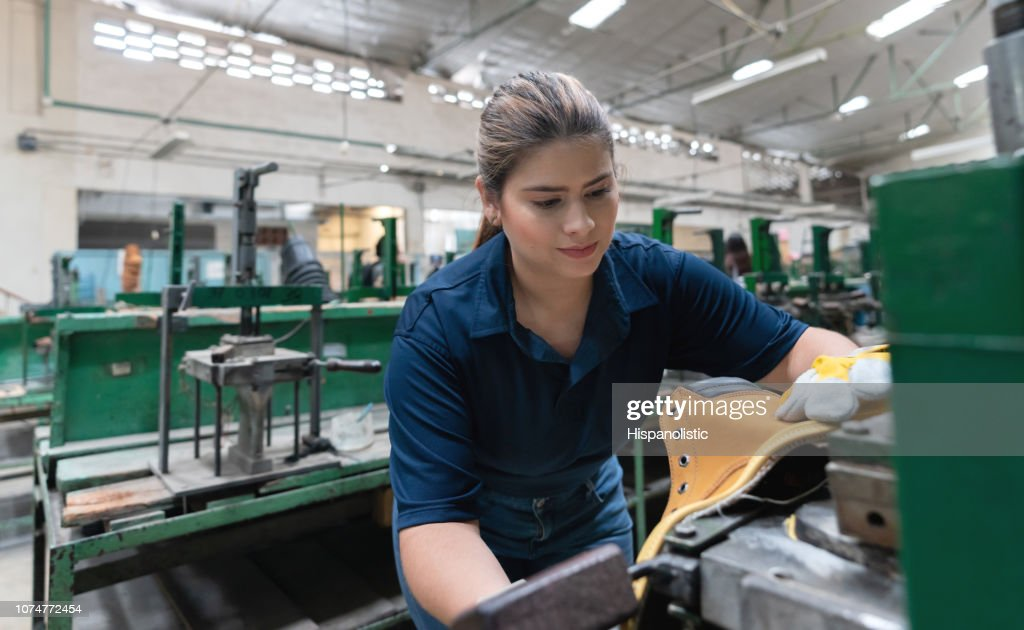 Pretty latin american cobbler producing boots at a shoe factory : Stock Photo