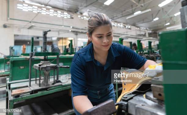 Pretty latin american cobbler producing boots at a shoe factory