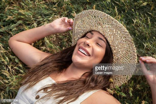 pretty latina woman laughing in the grass - golden hour stock pictures, royalty-free photos & images