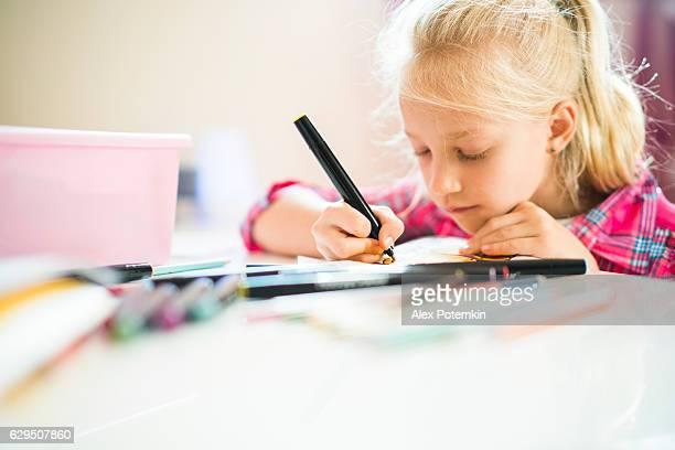 Pretty little girl do homework in the kids room