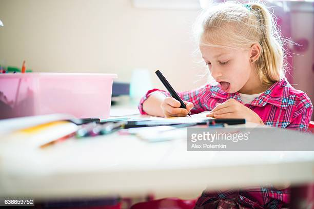 Pretty little girl drawing in the kids room