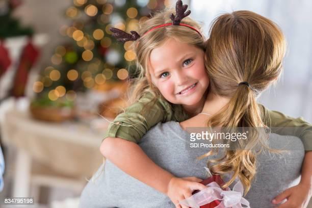 Pretty little girl gives her mom a big hug on Christmas Eve