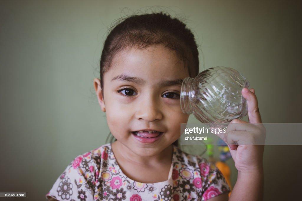 Pretty little girl holding empty glass jar. : Stock Photo