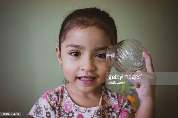 Pretty little girl holding empty glass jar.