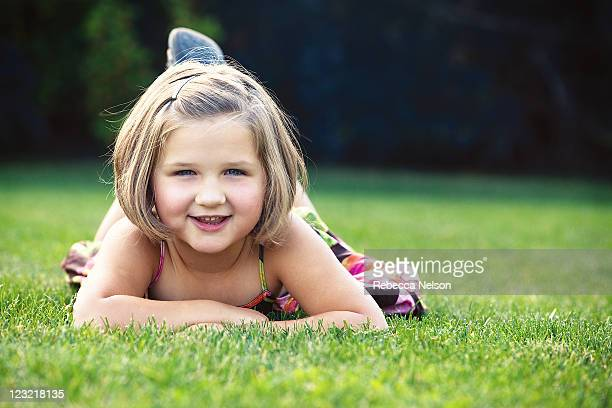 pretty little girl lying on grass - rebecca nelson stock pictures, royalty-free photos & images