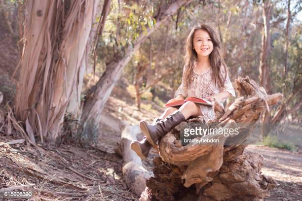 Pretty little girl outdoors happily reading a book
