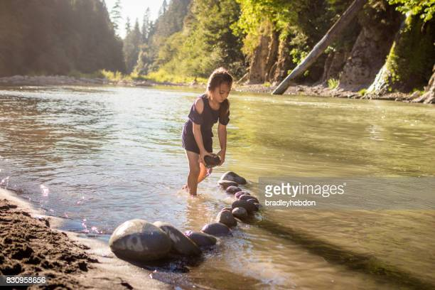 Pretty little girl playing with rocks in calm Oregon river