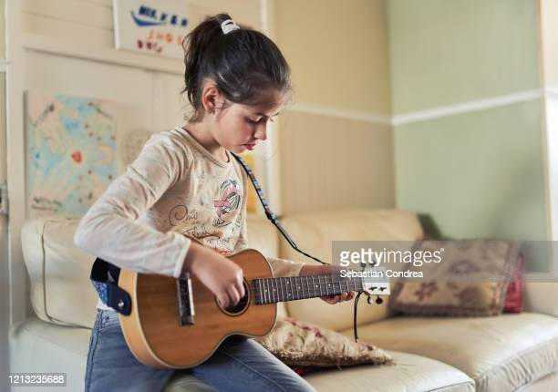 pretty little girl practicing some new sound on a guitar at home, uk, quarantin covid-19, - musical symbol stock pictures, royalty-free photos & images
