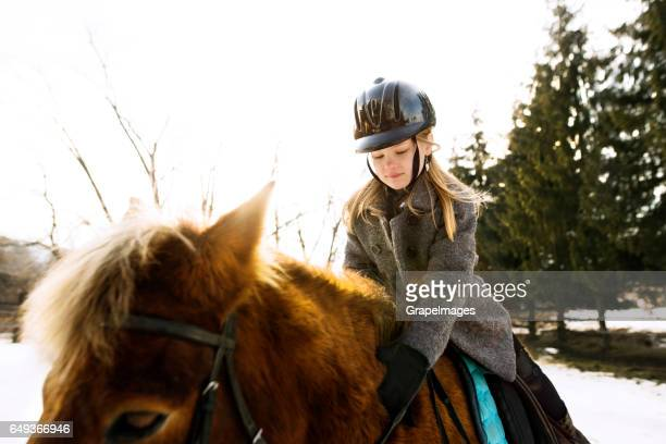 pretty little girl roding a horse on sunny winter day. - children only stock pictures, royalty-free photos & images