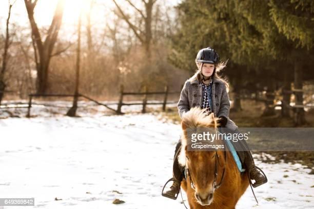 Vrij kleine meisje roding een paard op zonnige winterdag.