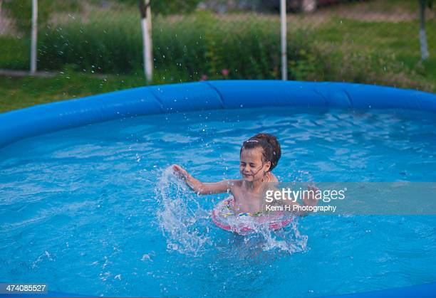 Pretty little girl swimming in outdoor pool