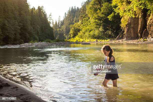 Pretty little girl wades through calm river in Oregon
