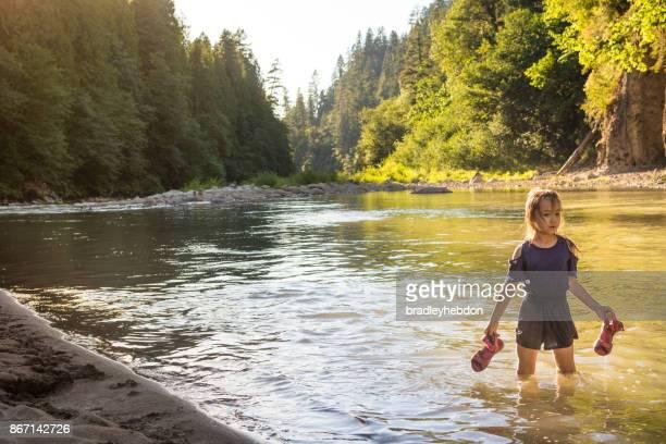 Pretty little girl wades through calm river in Oregon