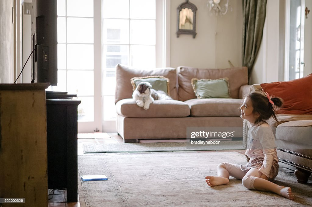 Pretty little girl watching a DVD on TV at home : Stock Photo