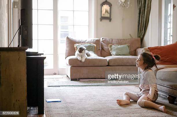 pretty little girl watching a dvd on tv at home - persian rug stock photos and pictures