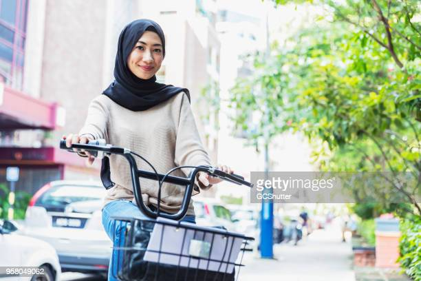 pretty malaysian girl riding her bicycle home - malaysia beautiful girl stock photos and pictures